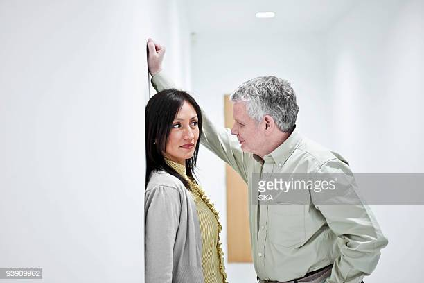 suggestive couple in corridor - sexual harassment stock pictures, royalty-free photos & images