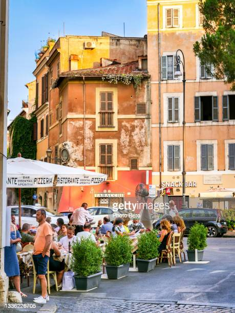 a suggestive glimpse of the rione monti in the heart of rome with a typical outdoor restaurant - image title stock pictures, royalty-free photos & images
