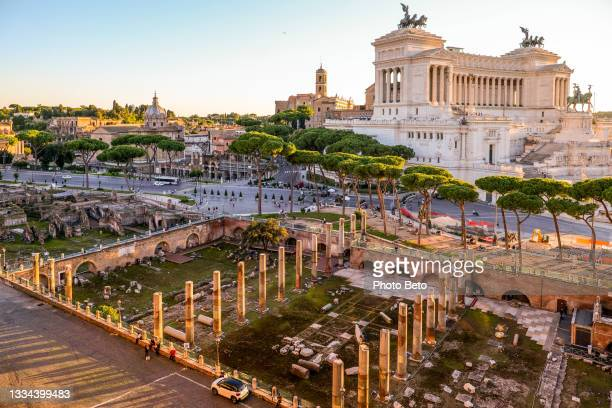 a suggestive sunset view of the trajan's forum and the altare della patria in the heart of rome - altare della patria stock pictures, royalty-free photos & images