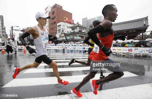 Suguru Osako Japanese national marathon record holder passes the Kaminari Gate at Sensoji Temple during the annual Tokyo Marathon on March 3 near the...