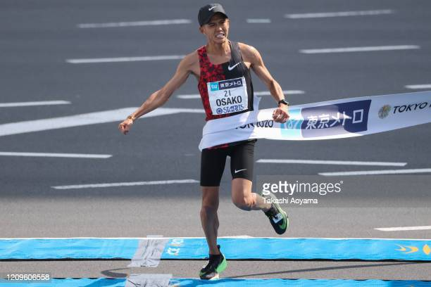 Suguru Osako of Japan celebrates as he crosses the finish line to take fourth place in the men's competition during the Tokyo Marathon on March 01...