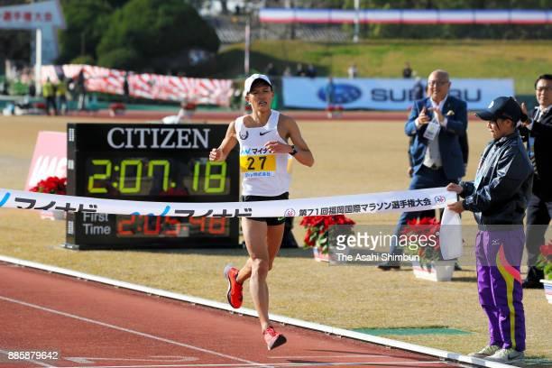 Suguru Osako of Japan crosses the finish tape to win the third place in the 71st Fukuoka International Marathon at Heiwadai Athletic Stadium on...