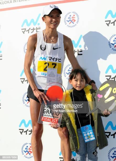 Suguru Osako of Japan is seen with his child after the third place finish in the 71st Fukuoka International Marathon at Heiwadai Athletic Stadium on...