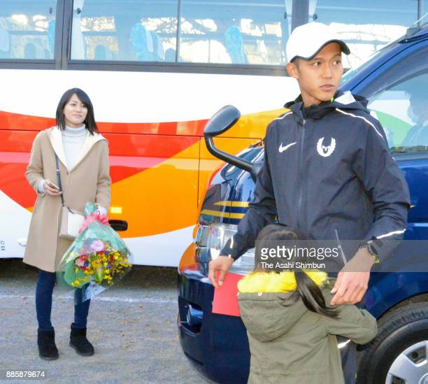 Suguru Osako of Japan is seen with his wife and child after the third place finish in the 71st Fukuoka International Marathon at Heiwadai Athletic...