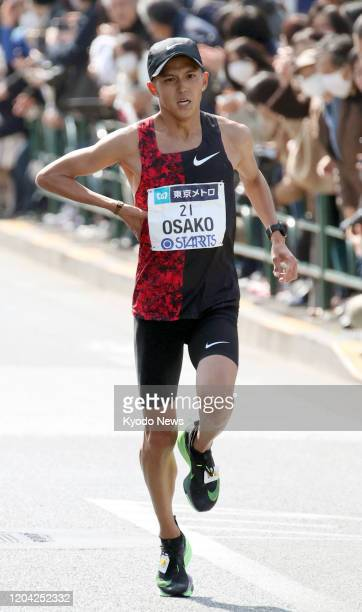 Suguru Osako of Japan massages his side with 4 kilometers remaining en route to finishing fourth and breaking his own national record at the Tokyo...