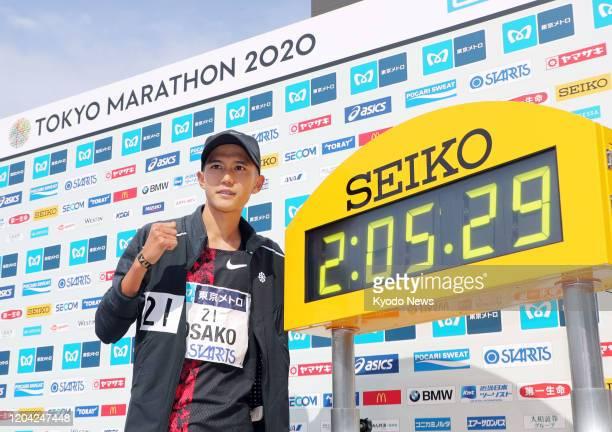 Suguru Osako of Japan poses next to a clock displaying his new national record at the Tokyo Marathon on March 1 2020