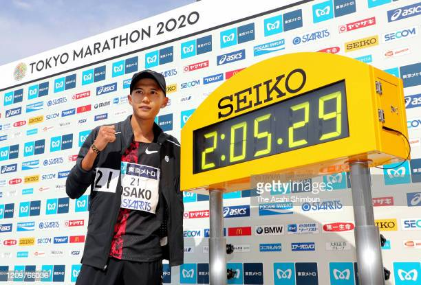 Suguru Osako of Japan poses with the clockdisplaying his new Japan record after competing in the Men's event after the Tokyo Marathon on March 1 2020...