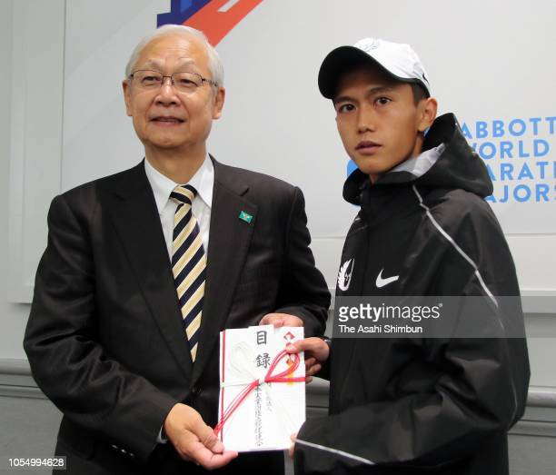 Suguru Osako of Japan receives the certificate of prize money to renew the Japan record from Koichiro Nishikawa president of the Japan Industrial...