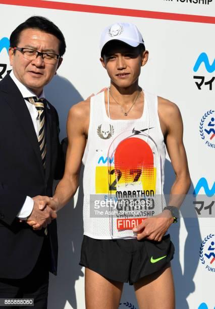 Suguru Osako of Japan shakes hands with Toshihiko Seko after the third place finish in the 71st Fukuoka International Marathon at Heiwadai Athletic...