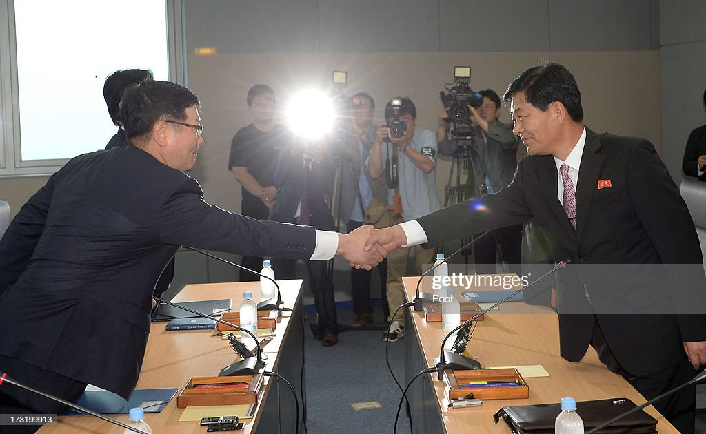 Suh Ho, the head of South Korea's working-level delegation (L) shakes hands with his North Korean counterpart Park Chol-Su (R) during their meeting at Kaesong Industrial District Management Committee on July 10, 2013 in North Korea. Government officals and business leaders from North and South Korea will hold talks today to discuss resuming operations at the Kaesong Joint Industrial Park 10 kilometres north of the border. North Korea withdrew over 50,00 of it's staff from the factories owned by Seoul in April of this year, and South Korea removed managers in May, during the height of tensions between the two nations. (Photo by Jung Yeon-Ho-Korea Pool/Getty Images).