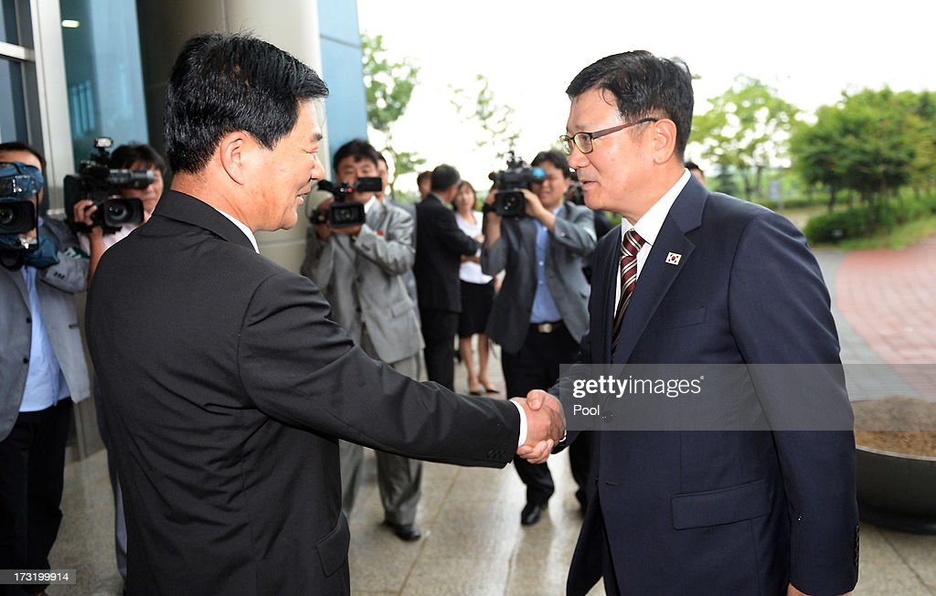 Suh Ho, the head of South Korea's working-level delegation (R) shakes hands with his North Korean counterpart Park Chol-Su (L) during their meeting at Kaesong Industrial District Management Committee on July 10, 2013 in North Korea. Government officals and business leaders from North and South Korea will hold talks today to discuss resuming operations at the Kaesong Joint Industrial Park 10 kilometres north of the border. North Korea withdrew over 50,00 of it's staff from the factories owned by Seoul in April of this year, and South Korea removed managers in May, during the height of tensions between the two nations. (Photo by Jung Yeon-Ho-Korea Pool/Getty Images).