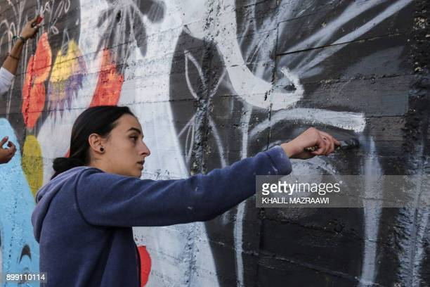 Suha Sultan a 20yearold graffiti artist and student uses a brush to draw a mural on a wall in the Jordanian capital Amman on December 16 2017 A tiny...