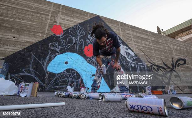Suhaib Attar a 25yearold graffiti artist and student picks up a canister of spray paint as he draws a mural on a wall in the capital Jordanian Amman...