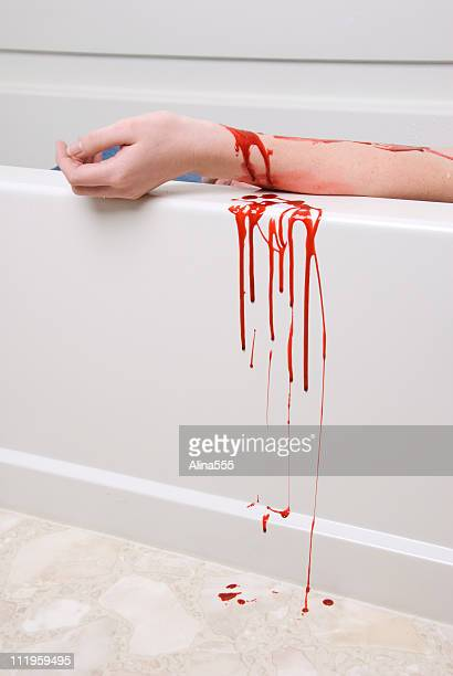 suicide concept: bleeding arm of a female in the bathtub - bloody hand stock photos and pictures