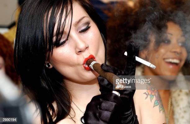 Suicide Girl Tegan lights a cigar backstage at The Trocedaro Theater February 4 2004 in Philadelphia PA The burlesque act is made up of six women...
