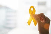 Suicide prevention and Childhood Cancer Awareness, Yellow Ribbon on wooden background  for supporting people living and illness. children Healthcare and World cancer day concept