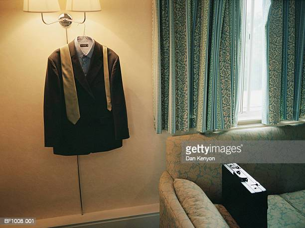 Suit and tie hanging on light fitting beside briefcase on sofa