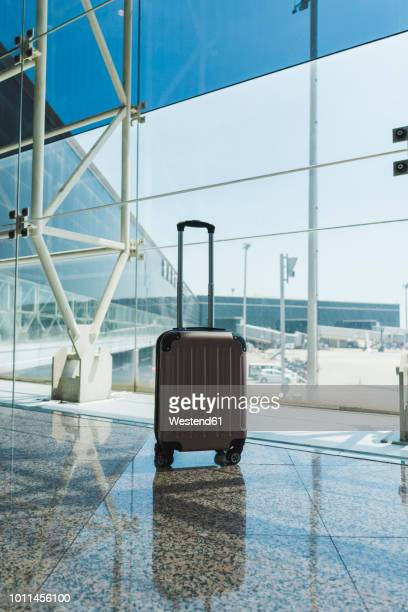 suitcase at airport - wheeled luggage stock photos and pictures