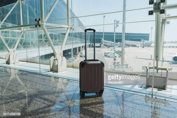suitcase at airport - valigia foto e immagini stock