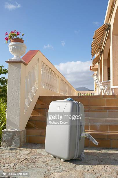 suitcase at bottom of steps leading to house - richard drury stock pictures, royalty-free photos & images