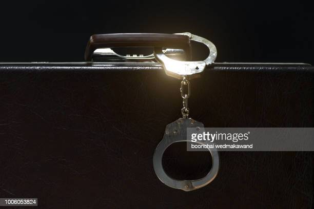 suitcase from pinned open handcuffs - corruption stock pictures, royalty-free photos & images