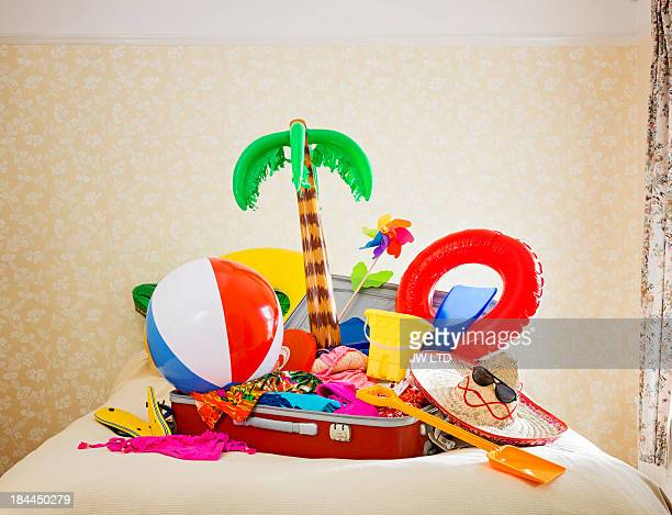 suitcase full of inflatable holiday props on bed - suitcase stock pictures, royalty-free photos & images