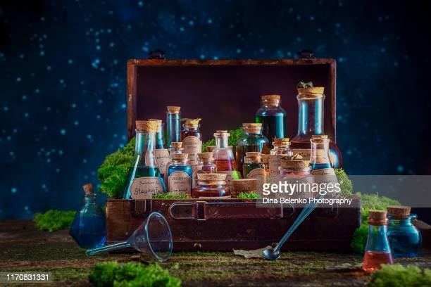 a suitcase full of potions and remedies for inspiration, motivation and productive work. modern witch concept with copy space. - potion stock photos and pictures