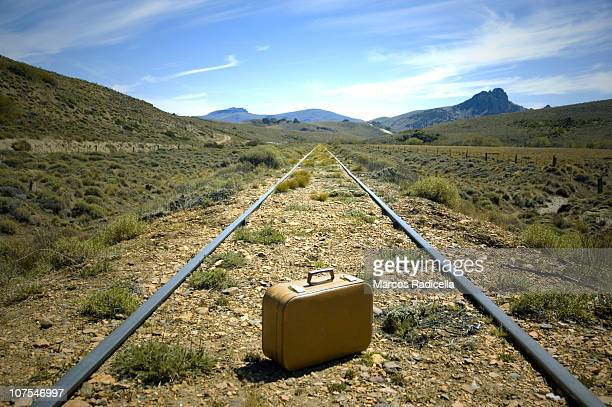 suitcase in the middle of railways in patagonia - radicella stock pictures, royalty-free photos & images