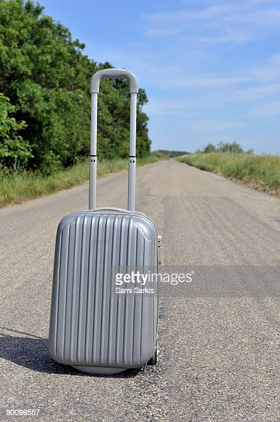 Suitcase on empty countryside road