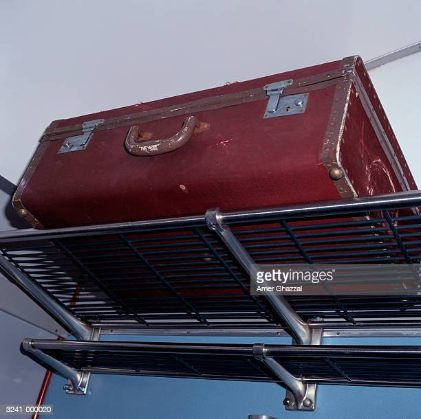 suitcase on luggage rack - luggage rack stock photos and pictures