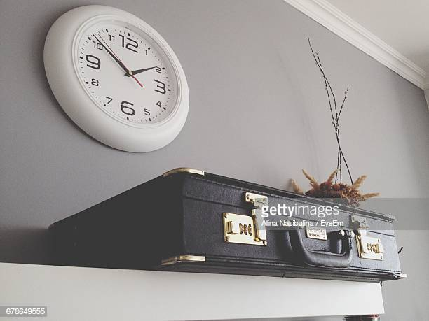 Suitcase On Shelf Against Clock Mounted On Wall