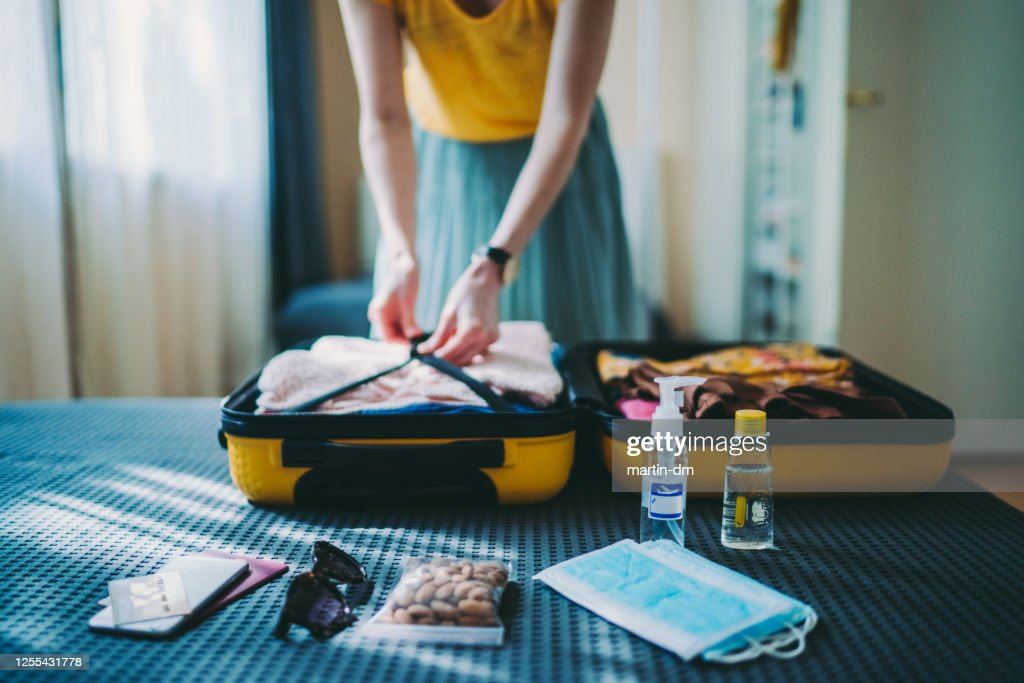 Suitcase packing for travel, COVID-19 : Stock Photo