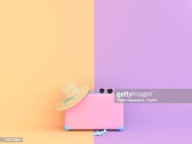 suitcase with hat against colored background - valise photos et images de collection