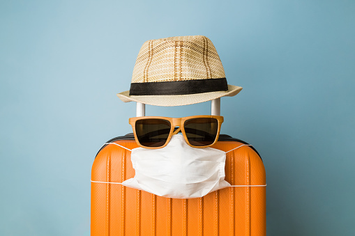 Suitcase with hat, sunglasses and protective medical mask on pastel blue background minimal creative coronavirus covid-19 travel concept. 1218246658