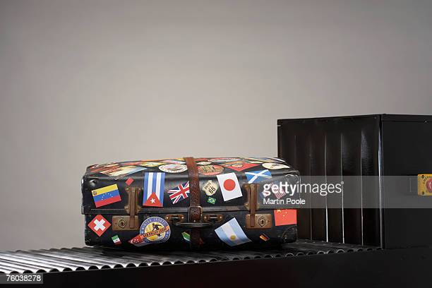 Suitcase with stickers of national flags on conveyor belt