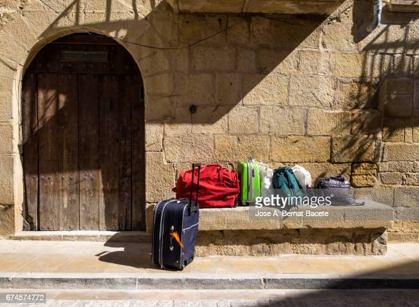 Suitcases and bags of trip in the street of a people in a trip of rural tourism at a bus stop
