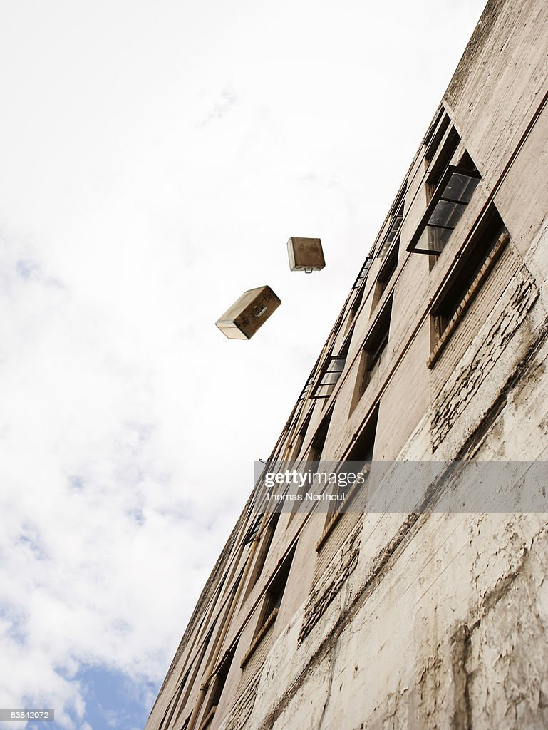 suitcases being thrown from a building : Stock Photo