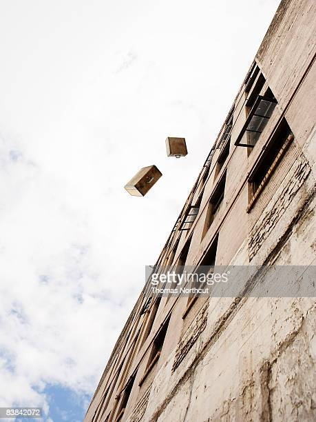 suitcases being thrown from a building