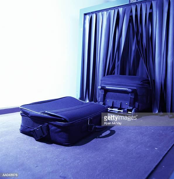 Suitcases passing through airport metal detector (blue tone)