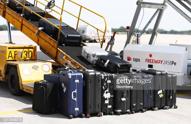 Suitcases sit on a luggage conveyor as they are loaded onto ab Airbus SE A350-900 'Braunschweig' passenger aircraft, operated by Deutsche Lufthansa...