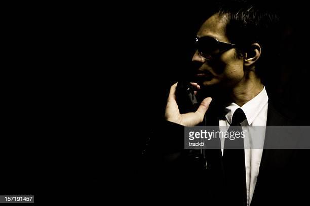 Suited hitman with gun hiding in a darkened corner watching...