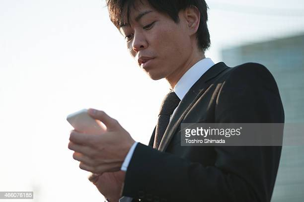 Suited man touching smart phone