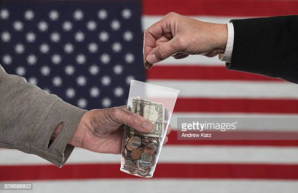 Suited man's hand placing penny into plastic cup filled with change held by dirty man's hand against US flag background