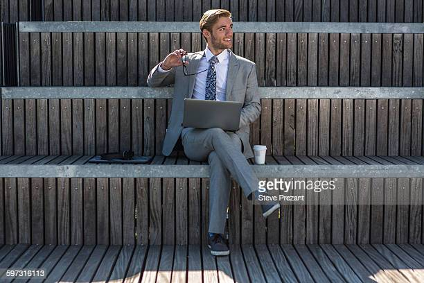 Suited young businessman using laptop on city stair