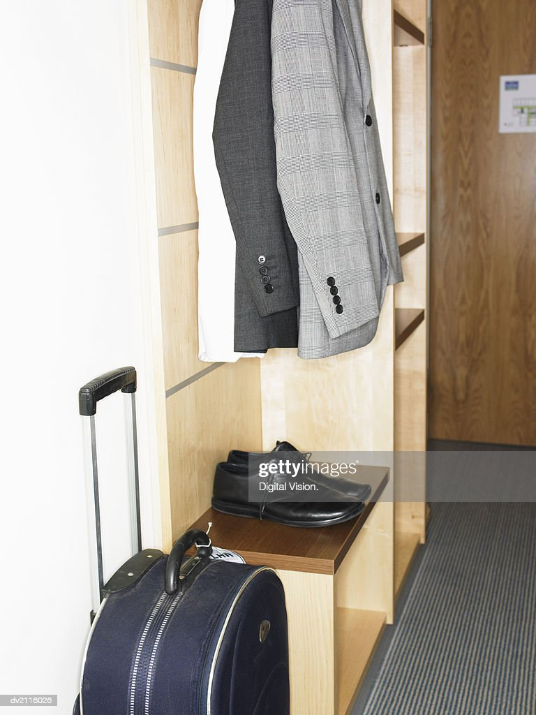 Suits, Shoes and Suitcase Stored in a Cabinet : Stock Photo