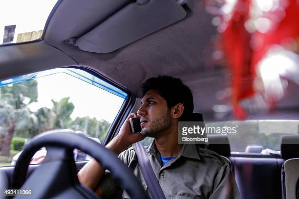 Sujas Kumar Singh a driver for the Uber Technologies Inc ridehailing service uses a mobile phone while sitting in a taxi in New Delhi India on Friday...