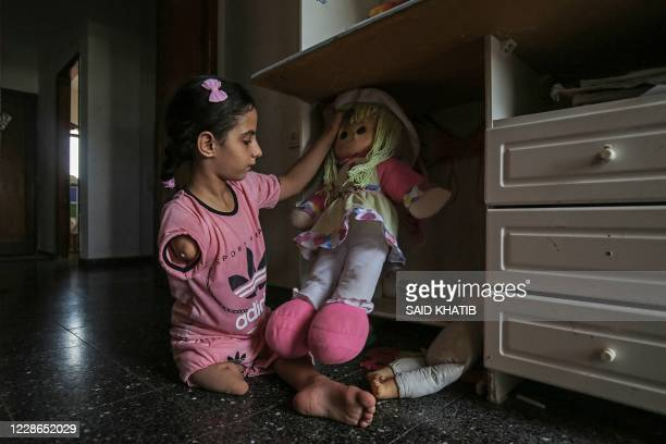 Sujud Qudada, a 10-year-old Palestinian girl suffering from congenital amputation, plays with her toy inside her room in the southern Gaza Strip city...