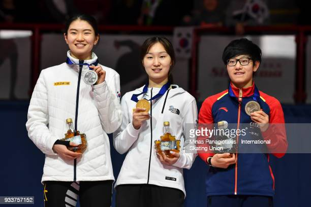 Suk Hee Shim of Korea Min Jeong Choi of Korea and Jinyu Li of China hold up their medals after completing the women's 3000 meter SuperFinal during...