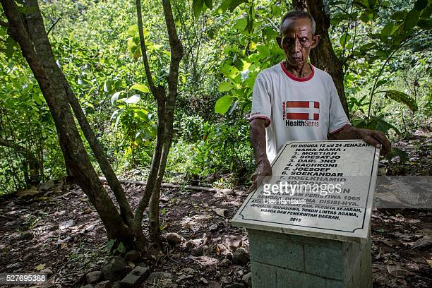 Sukar 83 years old a villager who witnessed Indonesia's anticommunist massacre stands next to the tombstone which was installed by activists and...