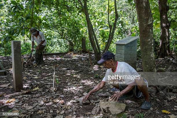 Sukar, 83 years old, a villager who witnessed Indonesia's anti-communist massacre, cleans near the tombstone which was installed by activists and...